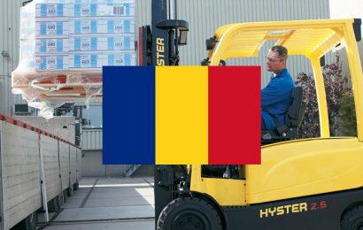 Meneer zit in een gele heftruck, de Roemeense vlag staat duidelijk centraal in beeld.