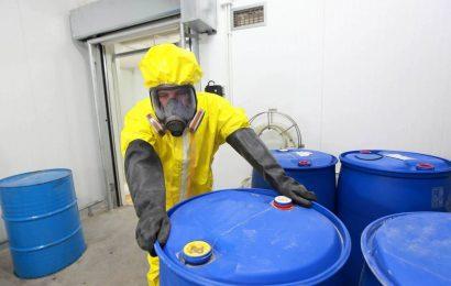Meneer werkt in een volledig beschermend geel pak met blauwe tonnen waar giftige stoffen in zitten.